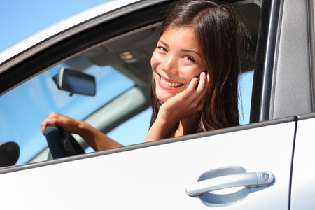 Car woman using smart phone while driving in car  Beautiful young woman talking on mobile phone smiling happy looking at camera  Mixed race eurasian woman  photo