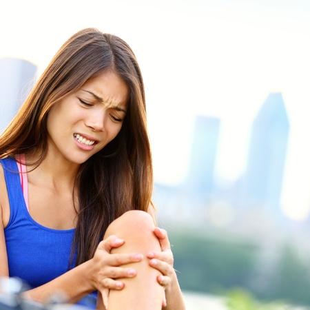 dolor de rodilla: Deportes La mujer herida con dolor en la rodilla del deporte conjunta de entrenamiento joven modelo de fitness mujer fuera Foto de archivo