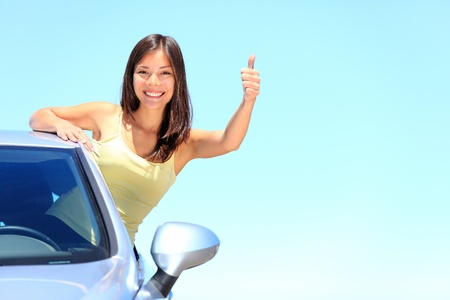 race car driver: Car  Woman driver happy smiling showing thumbs up coming out of car window on blue summer sky above the clouds  Beautiful young mixed race Caucasian   Chinese Asian woman  Stock Photo