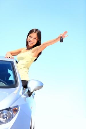 conducci�n: Conductor de coche de la mujer que muestra las llaves del coche sonriendo feliz en su nuevo coche y bella mujer de raza cauc�sica china asi�tica multirracial conducci�n mujer piloto en el d�a de la primavera o el verano