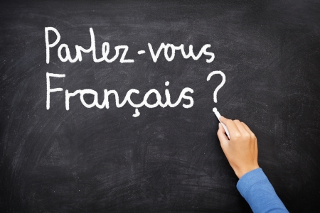 francais: Learning language - French. Learning French language concept of teacher or student writing parlez-vous francais (do you speak French) on blackboard  chalkboard.