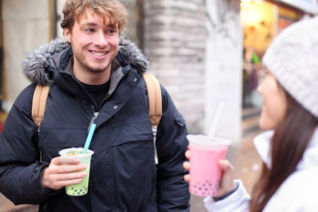 Friends in city drinking bubble tea  pearl milk tea smiling happy and talking in chinatown of Montreal, Quebec, Canada. photo
