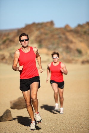 rates: Runners running training for marathon competition in beautiful desert landscape.  Stock Photo