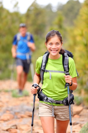 backpacking: Hiker woman. Hiking asian woman walking with hiking poles and hiking backpack smiling happy outdoors in nature. Hiker in background. Stock Photo
