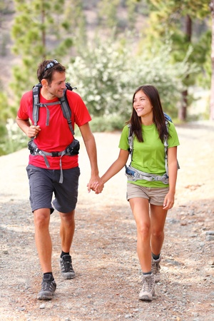 Young hikers smiling happy holding hands walking in forest during camping travel. photo