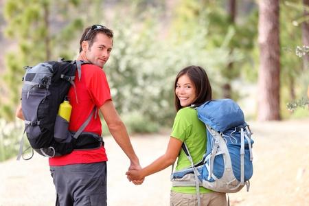 バックパック: ハイカー。キャンプ旅行の間に森を歩くハイキング若いカップルのハイキングします。アジアの女性と手を繋いでいる白人男性の健康的なライフ スタイルの写真。