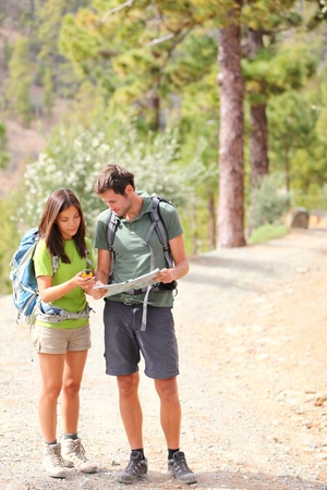Hikers - hiking couple looking at map using GPS to navigate during camping travel hike.