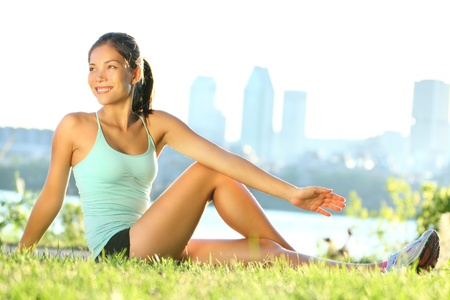 stretches: Stretching woman in outdoor exercise smiling happy doing yoga stretches after running.  Stock Photo
