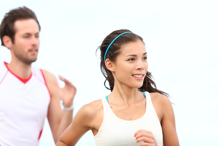 Runners jogging. Young couple running outside training for marathon. Stock Photo - 12720495