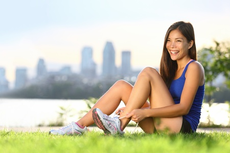 Woman runner happy tying running shoes before outdoor workout. photo