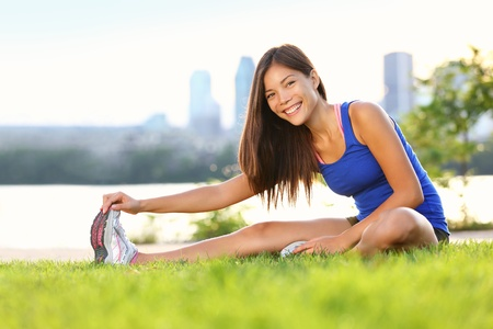 hamstring: Exercise woman stretching hamstring leg muscles duing outdoor running workout.