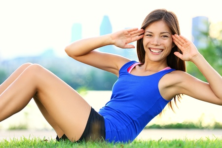 ups: Exercise woman doing situps in outdoor workout training.  Stock Photo