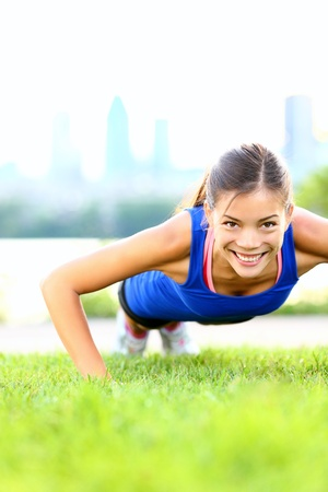 push up: Exercise woman doing situps in outdoor workout training.  Stock Photo