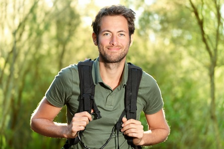 Young man hiking smiling happy portrait. Male hiker walking in forest. photo