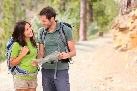 Happy couple hiking looking at map  Young interracial couple hikers smiling happy walking in forest during spring or summer  Asian woman, Caucasian man  photo