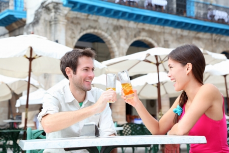 Cafe couple drinking talking having fun laughing smiling happy  Young interracial couple on travel vacation drinking rum in Old Havana, Cuba, Plaza de la Catedral  photo
