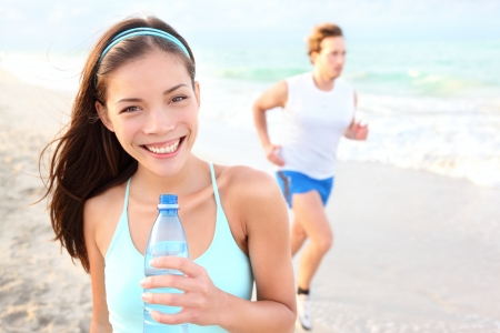 Runner woman drinking on beach with man running in background  Happy smiling mixed race Asian   Caucasian female fitness sport model during outdoor workout Stock Photo - 12902949
