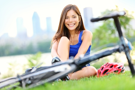 racing bike: Woman going biking on road bike  Smiling sport fitness model smiling outside in city park in Montreal, Quebec, Canada Stock Photo