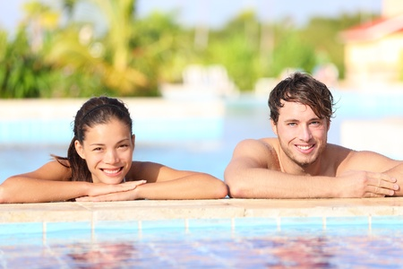 bikini pool: Young couple in pool - summer travel photo of two happy smiling people relaxing in tropical resort swimming pool  Caucasian man, Asian woman, focus on male model
