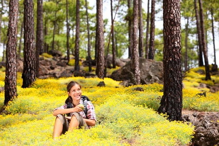 hiker: Woman hiker sitting relaxing after hiking eating apple in spring flowers in forest floor  Forest landscape, From Tenerife, Canary Islands, Spain