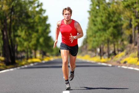 Running fitness sport man  Male runner sprinting on road - fit muscular male model training for marathon running fast on beautiful road in nature  photo