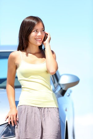 Woman on smart phone by car   Young woman standing by car talking on mobile phone  Happy smiling mixed race Caucasian Asian woman on a beautiful bright sunny summer day photo