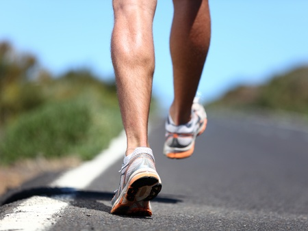 Running sport shoes on runner  Legs and running shoe closeup of man jogging outdoors on road