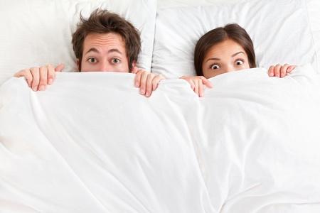 lit: Dr�le de couple dans le lit � la recherche et jeter un oeil sur des feuilles surpris jeune couple interracial, femme asiatique, homme de race blanche