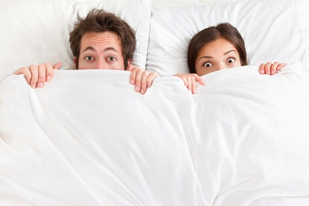 pareja en la cama: Pareja divertida en la cama mirando y mirando sobre hojas sorprendi� Pareja joven interracial, mujer asi�tica, hombre de raza cauc�sica Foto de archivo