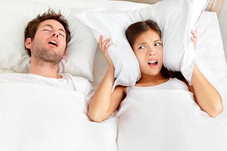 insomnio: Pareja ronquidos del hombre en la cama, roncando hombre y una mujer no puede dormir, que cubre los o�dos con la almohada para el ruido de ronquidos joven pareja interracial, mujer asi�tica, hombre de raza cauc�sica para dormir en la cama en su casa Foto de archivo
