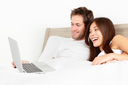 Happy couple with laptop in bed watching fun movie on computer in bed before sleeping  Smiling young interracial couple, Asian woman, Caucasian man in bed at home  photo