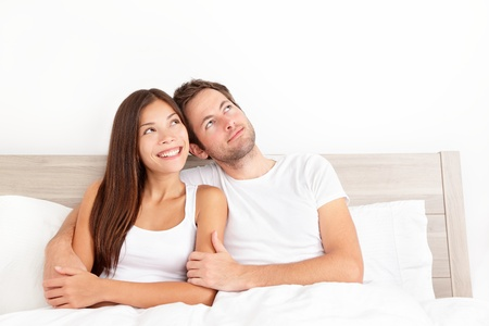 imagining: Happy couple in bed thinking and dreaming together looking up at copy space   Smiling young interracial couple, Asian woman, Caucasian man in bed at home