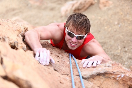 Climbing  Male climber rock climbing cliff wall with climb rope  Strong man climber on the way to summit at success  photo