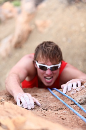 obstacles: Man climbing  Strong male climber in difficult challenge during rope rock climbing  Focus on hand in foreground