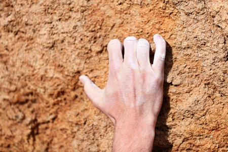 Climbing hand closeup grip during rock climbing  Male hand with chalk powder on rocks