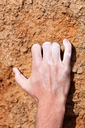 Climbing hand grip on rock  Male hand with chalk powder on rocks  photo