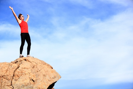 Success - winner reaching summit  Athlete in fitness sport clothes and running shoes reaching the goal cheering with arms raised  Man fitness model happy with lots of copyspace on blue sky