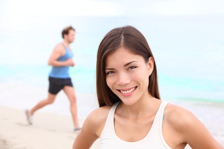 Runner workout woman portrait on beach with man running in background  Happy smiling mixed race Asian   Caucasian female fitness sport model during outdoor workout  photo