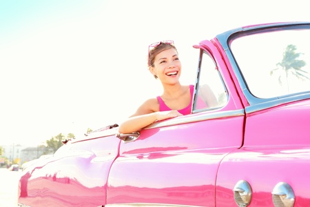 vintage cars: Vintage retro car woman driving in pink cabriolet old car smiling happy in Havana, Cuba. Stock Photo