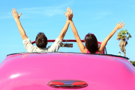 Freedom - happy free couple in car driving in pink vintage retro car cheering joyful wih arms raised. Friends going on road trip travel on summer day under sun blue sky. Stock Photo