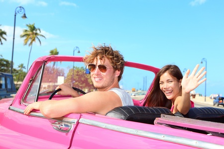 goodbye: Couple happy in vintage retro convertible car. Friends driving on summer road trip in pink car. Beautiful young Caucasian man and Asian woman model smiling joyful on sunny summer day travelin Havana, Cuba.