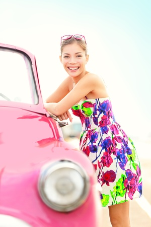 sundress: Vintage woman and car. Cute pink old vintage car and beautiful young retro woman smiling happy on sunny summer travel day. Pretty mixed race Asian  Caucasian female driver in Havana, Cuba.