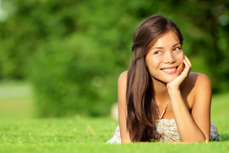 sun down: Asian woman lying in grass smiling happy looking at copy space. Beautiful girl in spring  summer relaxing and thinking. Mixed race Caucasian  Asian Chinese model outdoors.