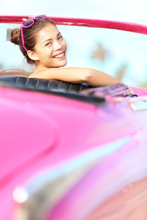Retro woman smiling happy in old pink vintage car driving on road trip on beautiful summer day. Pretty mulitracial Asian / Caucasian female model in Havana, Cuba photo