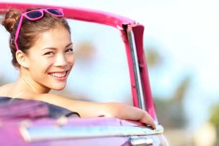 day trip: Car woman happy in old pink retro vintage car. Young woman driving on road trip on beautiful sunny summer day. Pretty mixed race Asian  Caucasian female model.