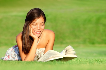 Reading. Woman reading book in park during spring  summer time. Happy smiling beautiful young university student studying lying down in grass. Beautiful mixed race Asian Chinese  Caucasian female model outdoors. photo
