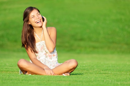 Phone woman laughing in talking in smart phone in park during spring  summer. Happy smiling beautiful young woman sitting in grass. Multiracial Caucasian  Chinese Asian female model outside in summer dress. photo