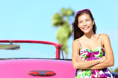 drivers: Car woman happy smiling by pink vintage car. Beautiful young multiracial female driver in Havana, Cuba.