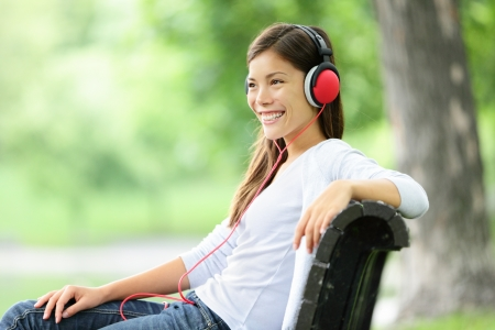 music listening: Woman listening to music in park wearing headphones smiling happy. Mixed race Asian Caucasian young woman relaxing outdoors enjoying spring.