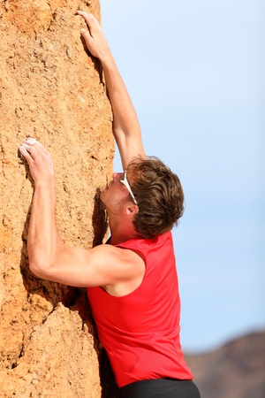 Climbing  Rock climber free climbing  Strong fit man fitness sport model hanging on vertical cliff  photo